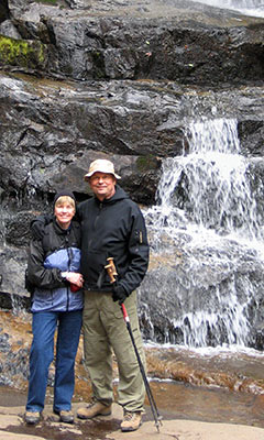 Sue and John hiking by a waterfall